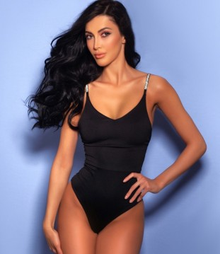 Model Bethany In A Black Swimsuit Against A Blue Background